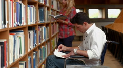 Disabled student reading in the library Stock Footage