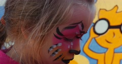Kitty-cat face painting for a girl on an International kite festival in Leba, Stock Footage