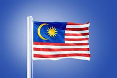 Flag of Malaysia flying against a blue sky - stock photo