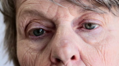 Close up of old woman's face, startled look and rapid blinking Stock Footage