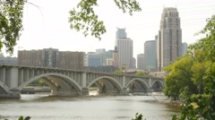 Wide shot of bridge leading to downtown Minneapolis from St. Anthony Main. - stock footage
