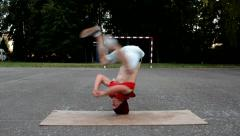 Crazy boy spins on his head on the street - stock footage