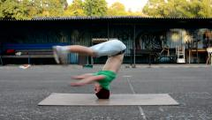 Crazy boy spins on his head on the street Stock Footage