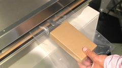 Stock Video Footage of Sealing machine - demonstration of sealing a carton package in a plastic bag