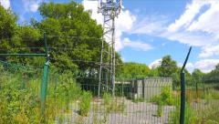 Stock Video Footage of Radio Transmitter In Fenced Area Trees Field Bushes Hand Held