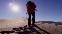 Female climber desert sun flare sky heat footprint shadow hiker Stock Footage
