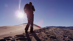 Traveller climber desert female sun flare trek hiker - stock footage