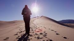 Desert female climber traveller sun flare adventure trek - stock footage