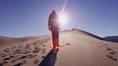 Trekking footprint desert hiker confident exploration sun flare Stock Footage
