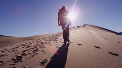 Desert traveller slow motion sand trek backpack mission - stock footage