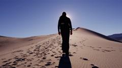 Female climber desert footprint sun flare sky sand shadow hiker - stock footage