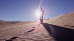 Traveller desert footprint sun flare sky heat adventure trek Stock Footage