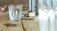 Asian woman with smartphone,ice coffee, tea,  water glass and cake at the bar Stock Footage