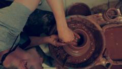 Young potter making a bowl from red clay. View from the top Stock Footage