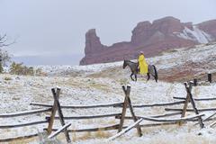 Cowboy Riding Horse in Snow, Rocky Mountains, Wyoming, USA - stock photo