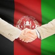 Businessmen handshake with flag on background - Afghanistan - stock photo