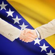 Businessmen handshake with flag on background - Bosnia and Herzegovina - stock photo