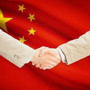 Businessmen handshake with flag on background - People's Republic of China - stock photo