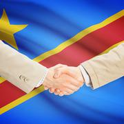 Businessmen shaking hands with flag on background - Democratic Republic of th - stock photo