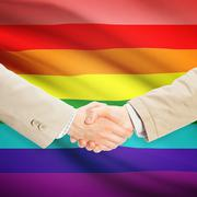 Businessmen handshake with flag on background - LGBT people - stock photo