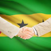 Businessmen handshake with flag on background - Sao Tome and Principe - stock photo