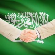 Businessmen handshake with flag on background - Saudi Arabia - stock photo