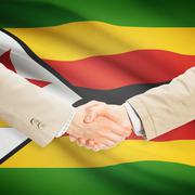 Businessmen handshake with flag on background - Zimbabwe - stock photo