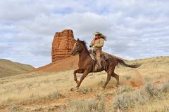 Cowgirl Riding Horse with Castel Rock in the background, Shell, Wyoming, USA - stock photo