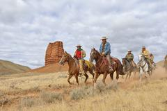 Cowboys and Cowgirls Riding Horses with Castel Rock in the background, Shell, - stock photo