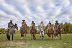 Cowboys and Cowgirls in a row Sitting on their Horses, Shell, Wyoming, USA - stock photo