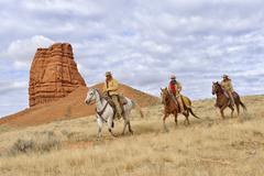 Cowboy and Cowgirls Riding Horses with Castel Rock in the background, Shell, - stock photo