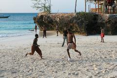African teens playing beach football on the banks Indian Ocean. - stock photo