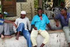 Several African men have a rest in the shade. - stock photo