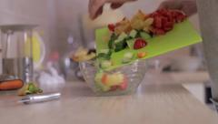 A hand fills the bowl with sliced vegetables - on the kitchen Stock Footage