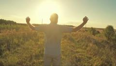 Man with arms raised looking at rural landscape - stock footage