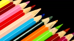 Top of line of colored pencils on black, reflection, rotation Stock Footage