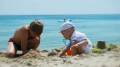 Child boy teen and kid baby child boy toddl playing in the sand on the sea beach Stock Footage