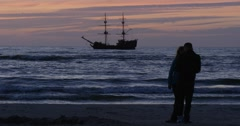 Couple Man And Woman Are Standing at The Sea Coastline Seaside Moving Ship on Stock Footage