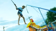 Child boy teen on rope jumping , children's attractions -slow moton  Stock Footage