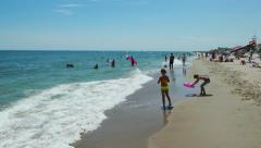 Holidaymakers, children, vacationers on the beach of sea, azure waves  - stock footage