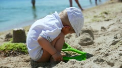Kid baby, child boy toddler playing in the sand on the sea beach  Stock Footage