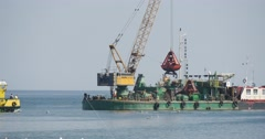 Yellow-Green Boat Floats To The Construction Barge With Crane On The Board Stock Footage