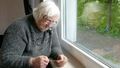 Senior woman is watching old pictures Stock Footage