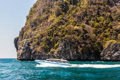 Cliff and speedboat - stock photo