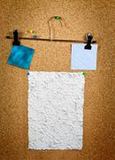 Paper of note with tack on cork noticeboard - stock photo