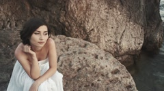 A beautiful bride standing on a cliff on the sea - stock footage