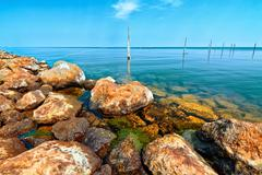 View of coast stones  in sea  with blue sky - stock photo