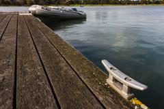 Mooring Bollard with Rubber Dinghy in the Background - stock photo
