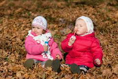 Two little girls blowing bubbles in the park - stock photo