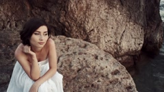 Woman standing on a cliff in a long white dress Stock Footage